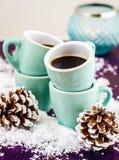 Kaffee in den kleinen Schalen im Weihnachtsdekor Lizenzfreie Stockfotos