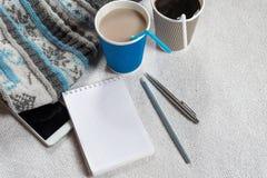 Kaffee in den Papierschalen, in gestricktem Schal und im Telefon auf einer weißen Tabelle stockbilder