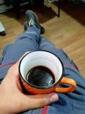 Kaffee an der Arbeitsorangenschale Stockfoto
