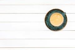 Kaffee in der blauen Schale auf weißem Holztisch Draufsicht, Kopienraum Stockbild