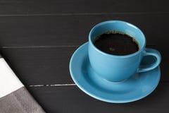 Kaffee in der blauen Schale mit zusammenpassendem Teller auf schwarzem hölzernem Hintergrund lizenzfreie stockfotos