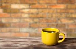 Kaffee in der gelben Schale auf Holztisch gegenüber von einem defocused Ziegelstein Stockbilder