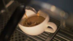 Kaffee, der oben in Schale von der Kaffeemaschine im Restaurantabschluß ausläuft stockfoto