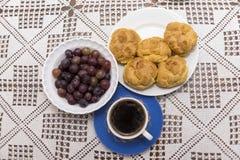 Kaffee in der Schale stößt mit Sahne auf einer Platte und Trauben in einer Schüssel luft Lizenzfreies Stockfoto