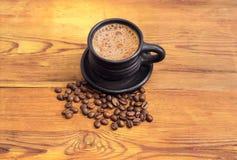 Kaffee in der schwarzen Schale und in den Kaffeebohnen auf Holzoberfläche Stockfotos