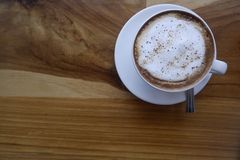 Kaffee in der weißen Schale auf Holztisch lizenzfreies stockbild