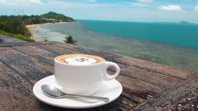 Kaffee in der weißen Schale auf Platte mit Löffel auf hölzerner rustikaler Tabelle, Seehintergrund mit der Palme-Bewegung Sch?n stock video