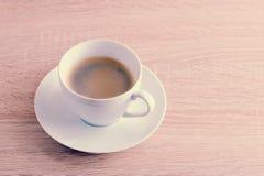 Kaffee in der weißen Schale mit Untertasse auf einem hölzernen Hintergrund Lizenzfreie Stockfotografie