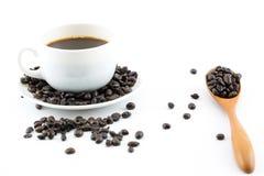 Kaffee in der weißen Schale und in den Kaffeebohnen Lizenzfreie Stockfotografie