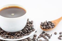 Kaffee in der weißen Schale und in den Kaffeebohnen Stockfotografie