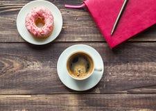 Kaffee, Donut und rosa Notizblock auf hölzernem Hintergrund Stockfotografie