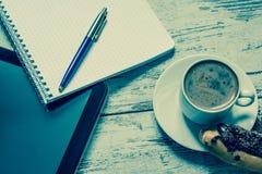 Kaffee, Eclair mit Schokolade, Tablette, Notizbuch und Stiftnahaufnahme auf hölzernem Hintergrund der Weinlese Beschneidungspfad  Lizenzfreie Stockbilder