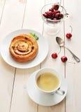 Kaffee in einem Becher, kleiner Kuchen mit Zimtkirschen Stockbilder