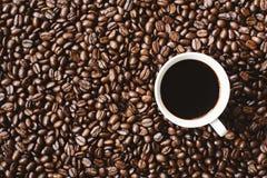 Kaffee in einem Cup auf Kaffeebohnehintergrund Stockbild