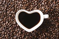 Kaffee in einer Herzformschale auf Kaffeebohnehintergrund Lizenzfreies Stockfoto
