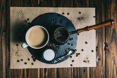 Kaffee in einer Reibe mit einer Schale auf einem dunklen Hintergrund mit Sahne lizenzfreies stockbild