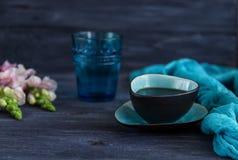 Kaffee in einer Türkisschale, in einem Glas Wasser und in den Löwenmäulern blüht auf einem schwarzen Hintergrund Freier Raum Stockfotografie