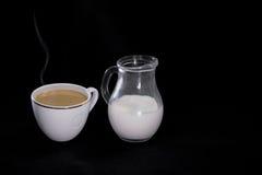 Kaffee in einer weißen Schalenmilch in einem kleinen Krug auf schwarzem Hintergrund Lizenzfreies Stockfoto