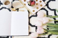 Kaffee, Erdbeeren, Notizbücher auf skandinavischer Wolldecke Rosa Tulpen und Goldlöffel Weißes schwarzes Muster- und Goldthema Le Lizenzfreie Stockfotos