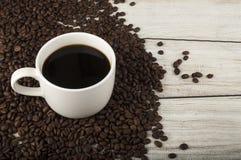 Kaffee füllte Schale und Bohnen auf hölzernem Hintergrund Lizenzfreie Stockfotos