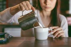 Kaffee-Geschäfts-Konzept - Nahaufnahmedame barista in vorbereitender und auslaufender Milch des Schutzblechs lizenzfreies stockbild