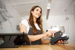 Kaffee-Geschäfts-Konzept - schönes weibliches barista, das Zahlungsservice für Kunden mit Kreditkarte und dem Lächeln gibt stockfotografie