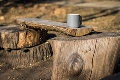 Kaffee im Freien auf einer Bank, die im Wald kampiert Stockbild