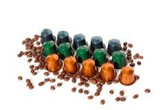 Kaffee kapselt verschiedene Farben und Kaffeebohnen auf dem weißen lokalisierten Hintergrund ein lizenzfreie stockfotografie