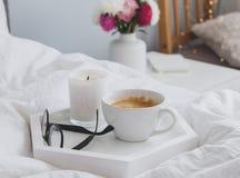 Kaffee, Kerze und Gläser auf dem Behälter, der auf dem Bett steht Stockfotos