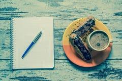 Kaffee, Kuchen, Eclair mit Schokolade, Notizbuch und Stiftnahaufnahme auf hölzernem Hintergrund der Weinlese Beschneidungspfad ei Lizenzfreies Stockbild