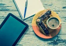 Kaffee, Kuchen, Eclair mit Schokolade, Tablette, Notizbuch und Stiftnahaufnahme auf hölzernem Hintergrund der Weinlese Beschneidu Stockfoto