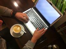 Kaffee am Laptop Stockbild