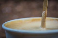 Kaffee Latte in der Papierschale mit hölzernem mischendem Stock Stockfotos