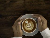 Kaffee Latte mit schöner Lattekunst an Hand stockfotografie