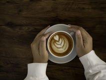 Kaffee Latte mit schöner Lattekunst an Hand lizenzfreie stockbilder