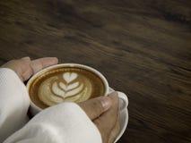 Kaffee Latte mit schöner Lattekunst an Hand lizenzfreie stockfotografie