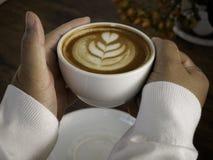 Kaffee Latte mit schöner Lattekunst an Hand lizenzfreie stockfotos