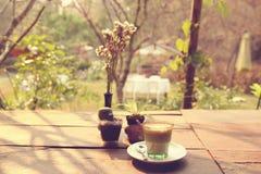 Kaffee Lattekunst auf dem hölzernen Beschaffenheitshintergrund - Weinleseeffekt Stockfotos