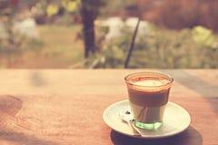 Kaffee Lattekunst auf dem hölzernen Beschaffenheitshintergrund - Weinleseeffekt Lizenzfreie Stockfotos