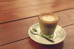 Kaffee Lattekunst auf der hölzernen Beschaffenheit Stockfotos