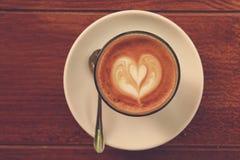 Kaffee Lattekunst auf der hölzernen Beschaffenheit Lizenzfreies Stockbild