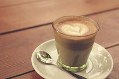Kaffee Lattekunst auf der hölzernen Beschaffenheit Lizenzfreies Stockfoto