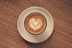 Kaffee Lattekunst auf der hölzernen Beschaffenheit Stockbild