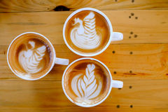 Kaffee Lattekunst auf hölzernem Tabellenbaum Stockbilder