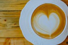 Kaffee Lattekunst auf hölzerner Schale Stockfoto