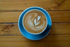 Kaffee Lattekunst auf hölzerner Tabelle Stockfoto