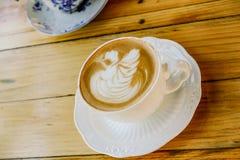 Kaffee Lattekunst auf hölzerner Tabellenschale lizenzfreie stockfotos