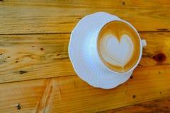 Kaffee Lattekunst auf hölzerner Tabellenschale Stockbild