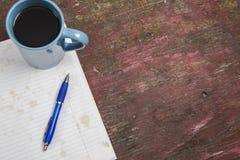 Kaffee mit beflecktem Notizblock und Stift mit Kopienraum Lizenzfreie Stockbilder