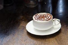 Kaffee mit Blumenmuster in einer weißen Schale auf hölzernem Hintergrund Lizenzfreie Stockfotografie